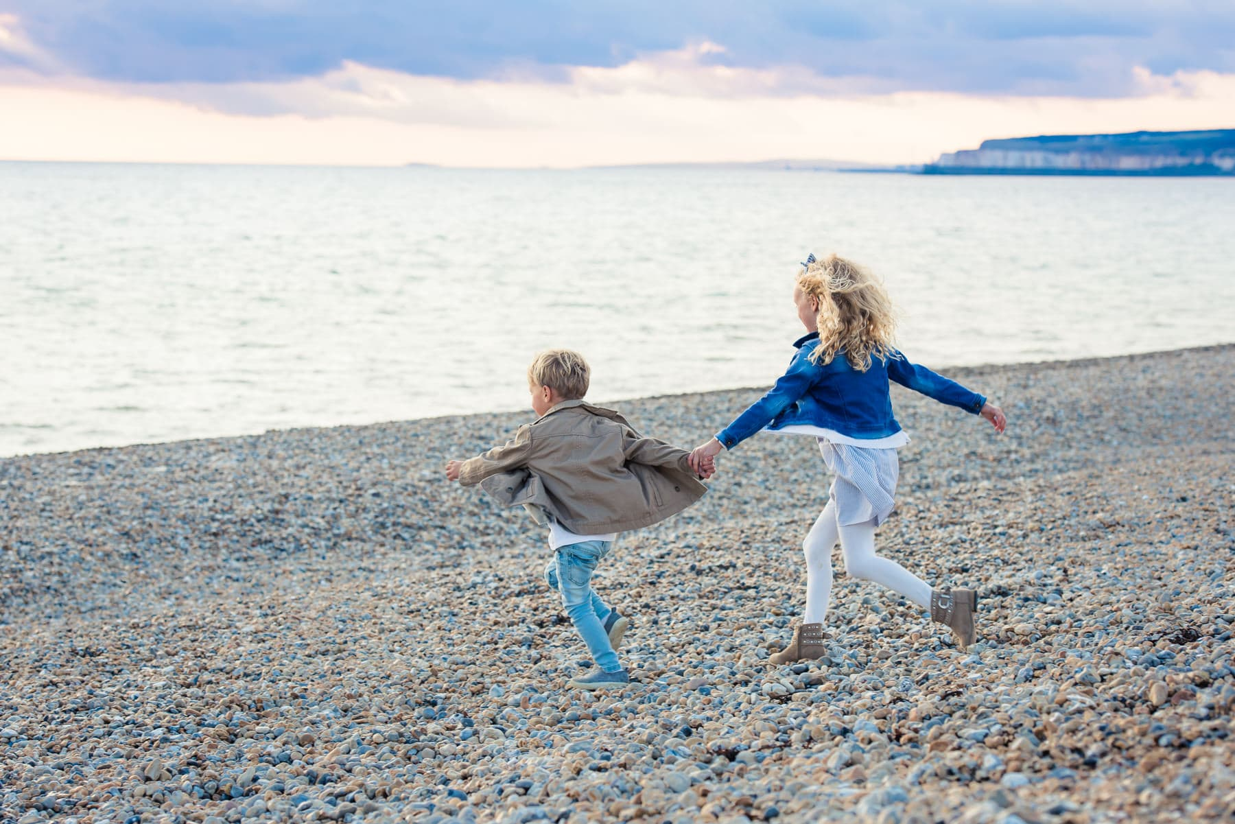 Boy and girl running into the sea holding hands